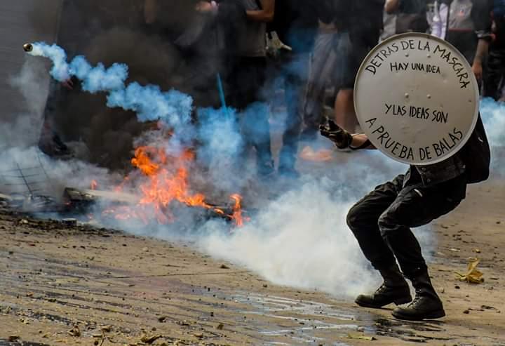Chico devolviendo bomba lacrimogena en manifestación de santiago de chile.